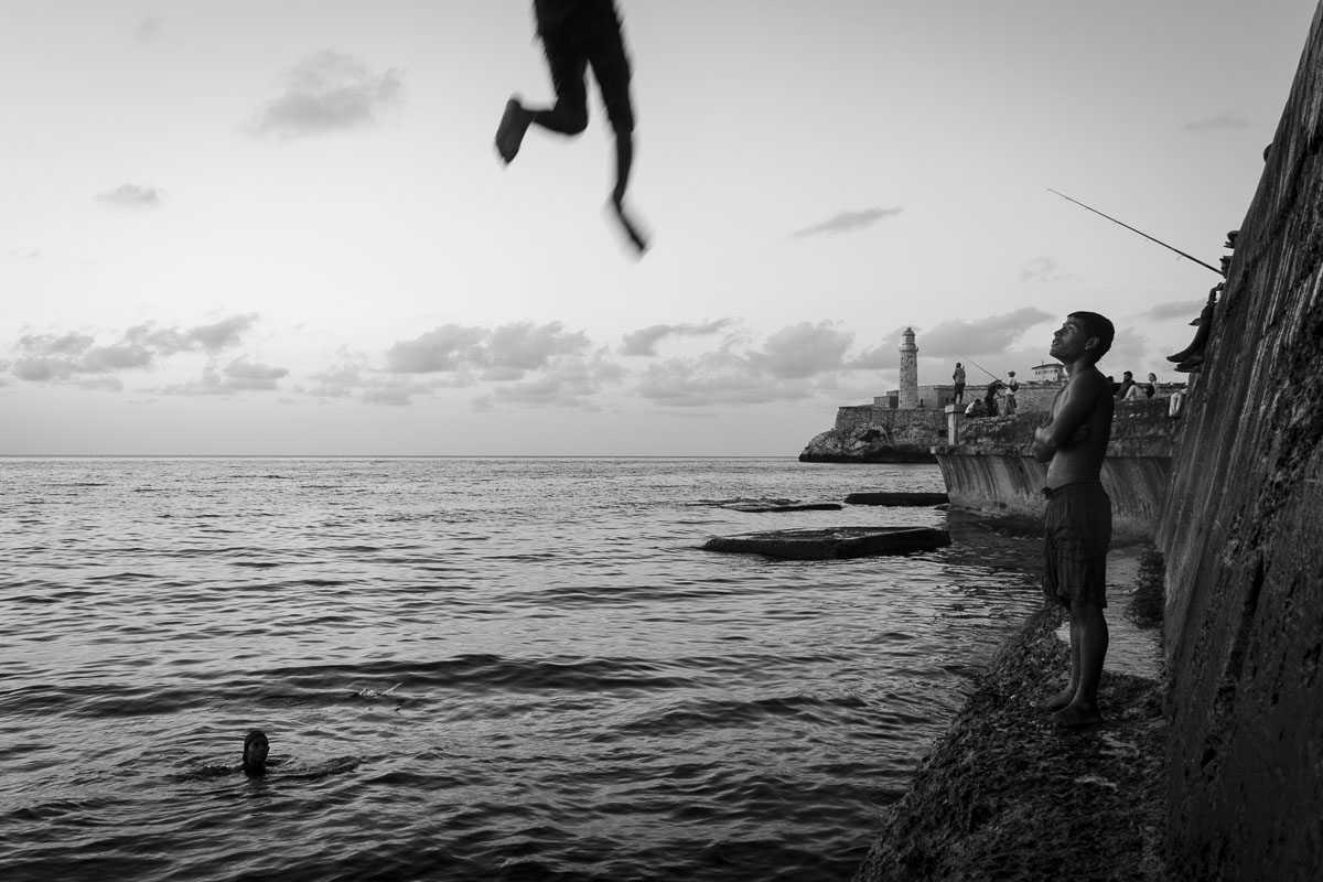 lighthouse of havana and kid jumping - Jumpers - Last jump in Havana - Cuban Photography essay about the last jumpers in Malecon.